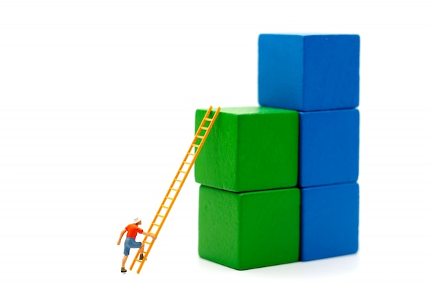 Pessoas em miniatura: alpinista, olhando para cima enquanto desafia a rota no gráfico de crescimento com escada de madeira, conceito do caminho para o objetivo e sucesso. Foto Premium
