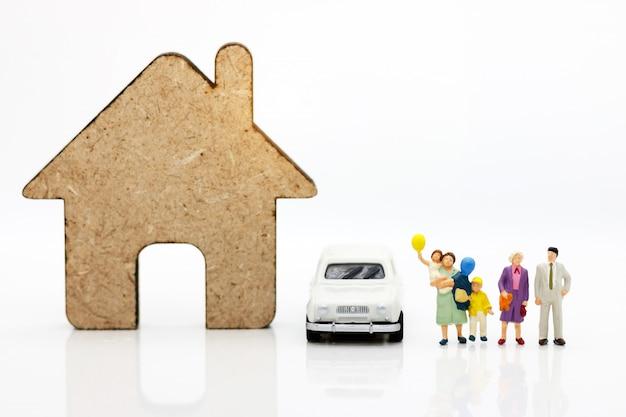 Pessoas em miniatura com a família em pé com casas e carros. Foto Premium