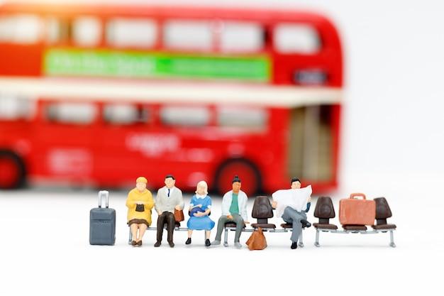Pessoas em miniatura com bagagem esperando o ônibus Foto Premium