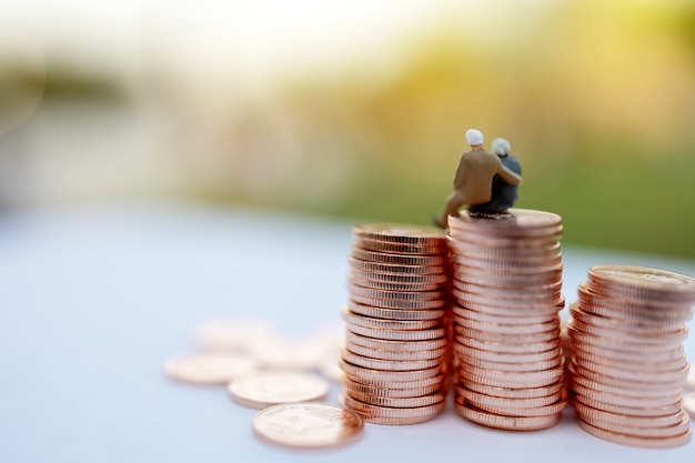 Pessoas em miniatura em moedas Foto Premium