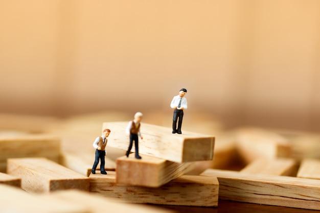 Pessoas em miniatura em pé em blocos de madeira Foto Premium