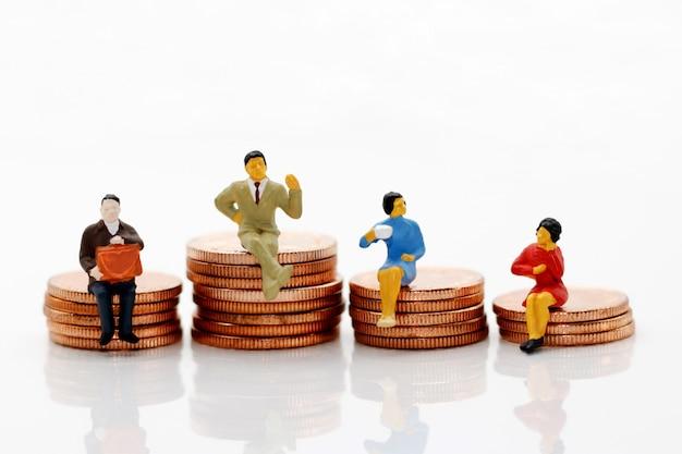 Pessoas em miniatura em pé em moedas Foto Premium