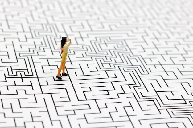 Pessoas em miniatura: empresária em pé no centro do labirinto. Foto Premium