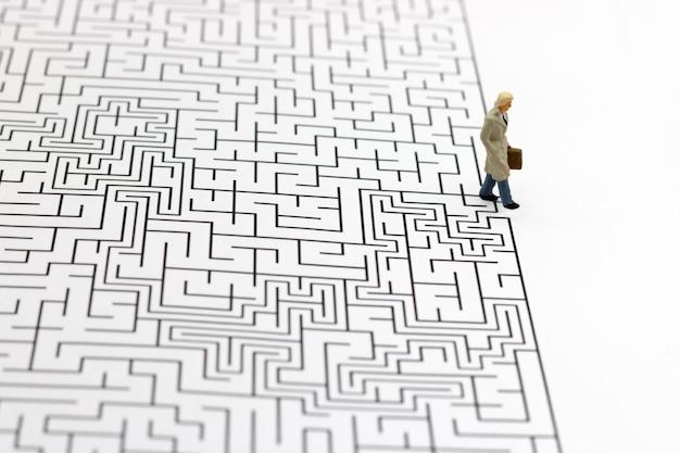 Pessoas em miniatura: empresário de pé no acabamento do labirinto. conceitos de encontrar uma solução, resolução de problemas e desafios. Foto Premium