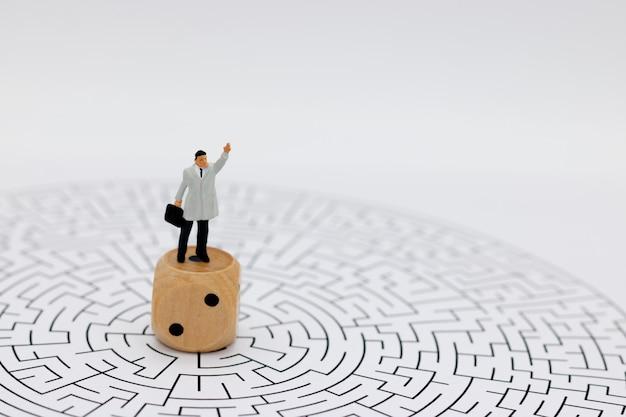 Pessoas em miniatura: empresário de pé no centro do labirinto com dados. Foto Premium