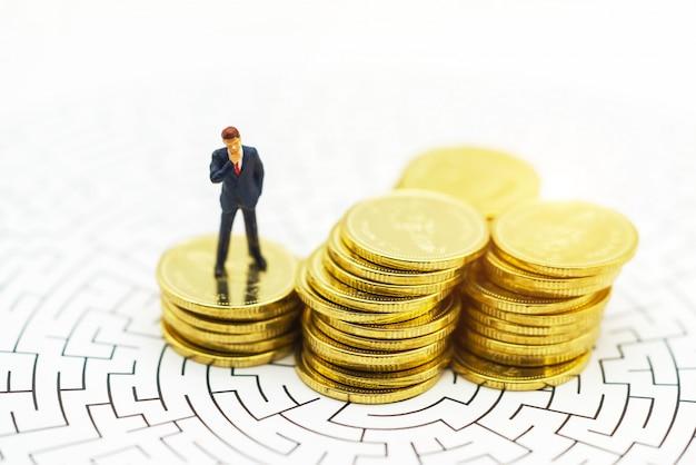 Pessoas em miniatura empresário de pé no centro do labirinto com pilha de moedas. Foto Premium