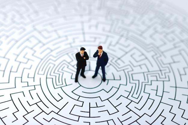 Pessoas em miniatura: empresário de pé no centro do labirinto. Foto Premium