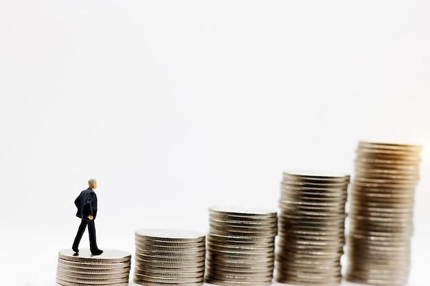 Pessoas em miniatura: empresário de pé no degrau do dinheiro da moeda. conceito de financeiro e dinheiro. Foto Premium