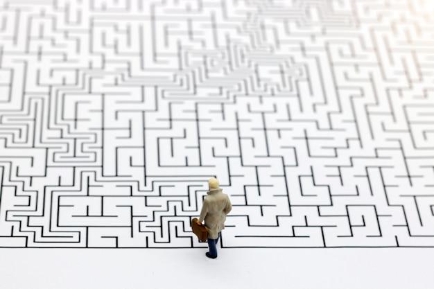 Pessoas em miniatura: empresário de pé no início do labirinto. Foto Premium