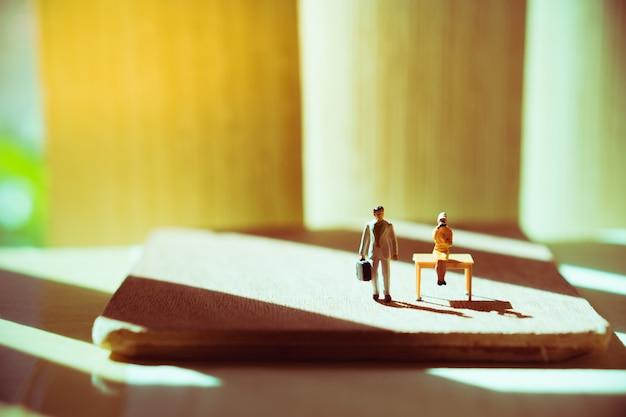 Pessoas em miniatura, empresário e mulher sentada na mesa usando para o conceito de recursos humanos de negócios - Foto Premium
