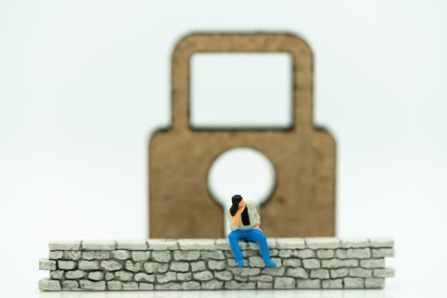 Pessoas em miniatura: empresário sentado na parede com chave mestra. Foto Premium