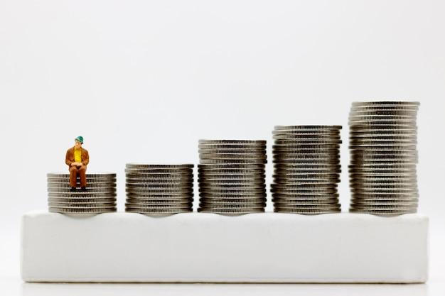 Pessoas em miniatura: empresário sentado no degrau do dinheiro da moeda. conceito de financeiro e dinheiro. Foto Premium