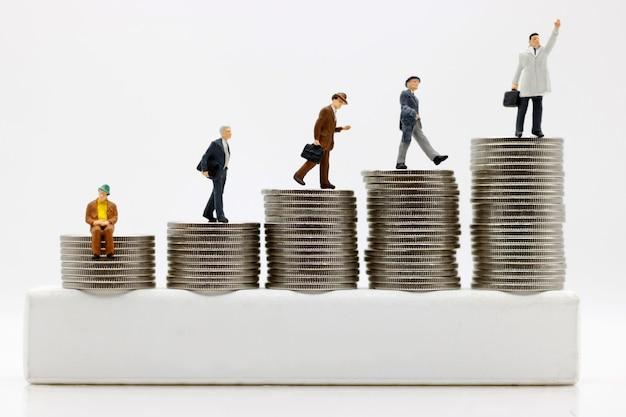 Pessoas em miniatura: empresários andando para o topo do dinheiro da moeda. conceito do caminho para o objetivo e sucesso, financeiro e dinheiro. Foto Premium