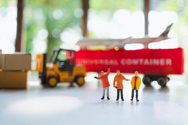 Pessoas em miniatura, equipe de técnicos em pé no veículo de transporte Foto Premium