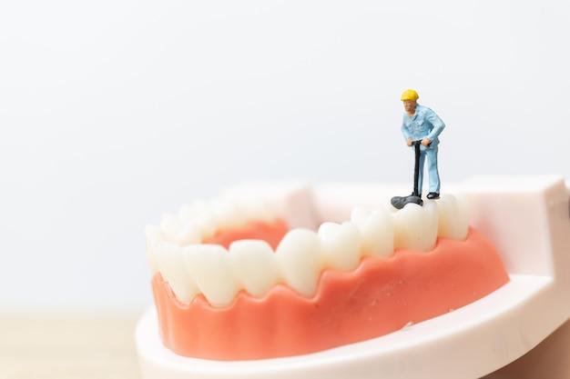 Pessoas em miniatura: equipe de trabalhador reparar um dente Foto Premium