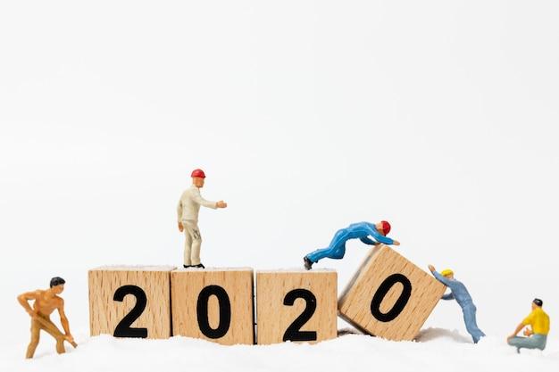 Pessoas em miniatura, equipe de trabalhadores criam número de blocos de madeira 2020 Foto Premium