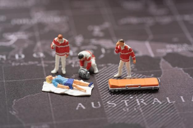 Pessoas em miniatura, equipe médica de emergência no trabalho na cena do acidente no mapa do mundo. Foto Premium