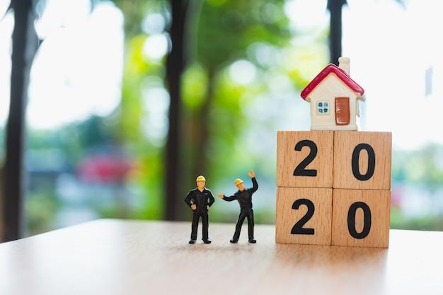 Pessoas em miniatura, especialista em casal em pé com mini casa e bloco de madeira ano 2020 usando como conceito de propriedade imobiliária Foto Premium