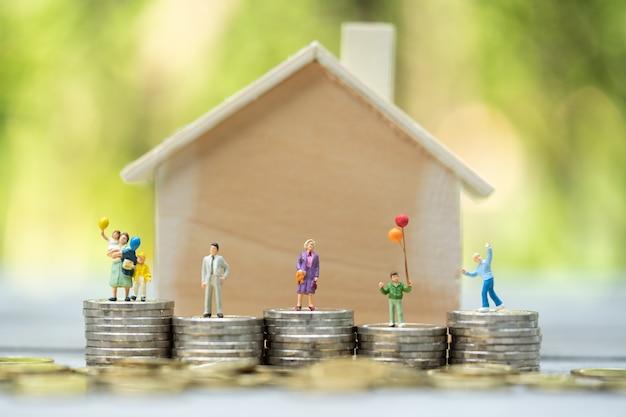 Pessoas em miniatura: família de pé em pilhas de moedas com modelo de casa na pilha superior. conceitos. conceito de escada de propriedade, hipoteca, investimento imobiliário, dinheiro, amor e dia dos namorados. Foto Premium