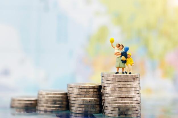 Pessoas em miniatura: família feliz, de pé na pilha de moedas, crescimento de poupar dinheiro. poupar dinheiro, educação, plano de emergência e conceito financeiro. Foto Premium