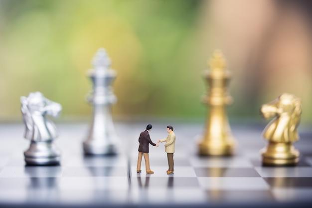 Pessoas em miniatura: figura de pequeno empresário em pé contra a parede do tabuleiro de xadrez com peças de xadrez Foto Premium