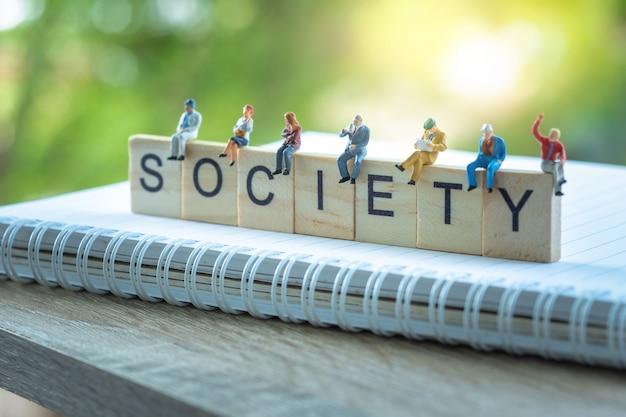 Pessoas em miniatura, grupo de pessoas de negócios, sentado em blocos de madeira com a palavra sociedade. Foto Premium