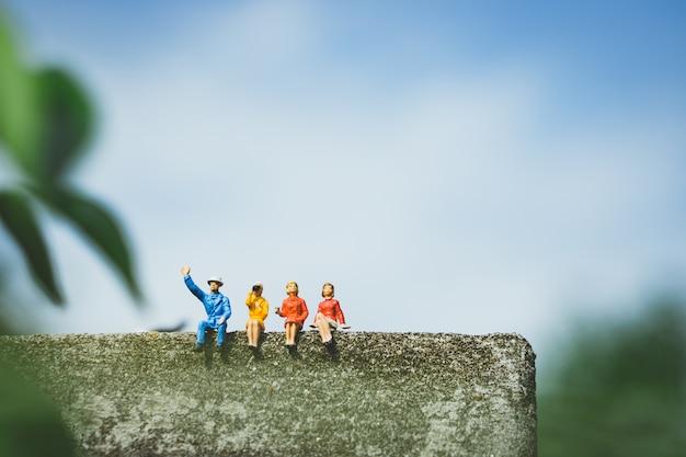 Pessoas em miniatura - grupo de pessoas sentadas na parede Foto Premium