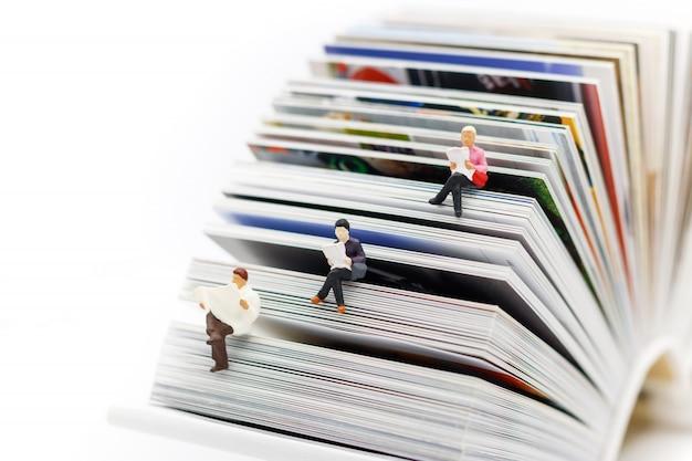 Pessoas em miniatura, lendo com o conceito de livro, educação ou negócios Foto Premium