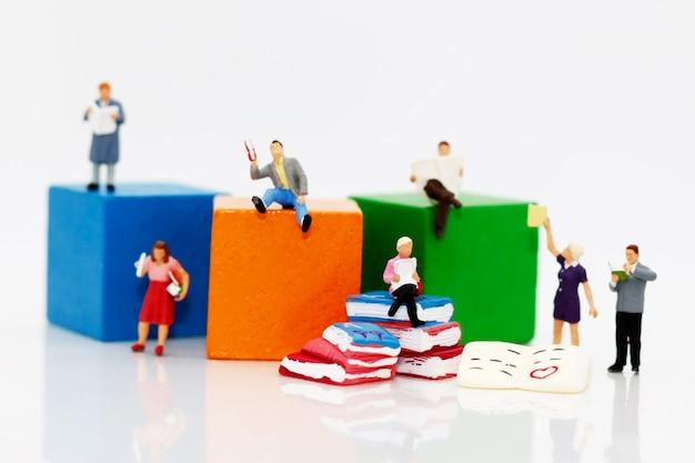 Pessoas em miniatura, lendo livros Foto Premium