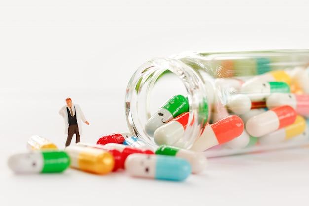 Pessoas em miniatura: médico com drogas usando como conceito médico de fundo Foto Premium