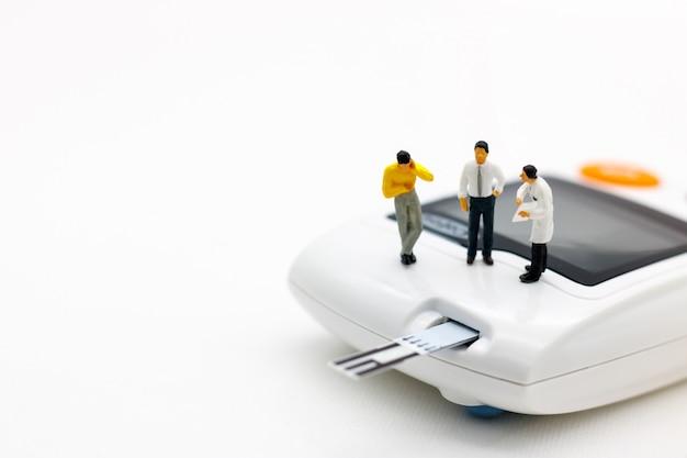 Pessoas em miniatura: médicos em pé com medidor de glicose de diabetes e agulha de injeção. Foto Premium