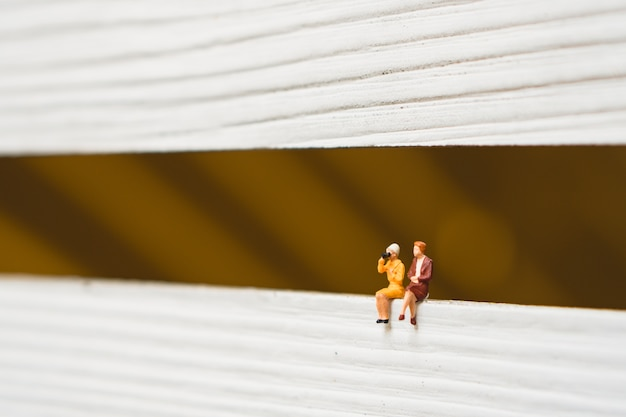 Pessoas em miniatura, mulher de casal sentado usando para conceito de recursos humanos de negócios Foto Premium