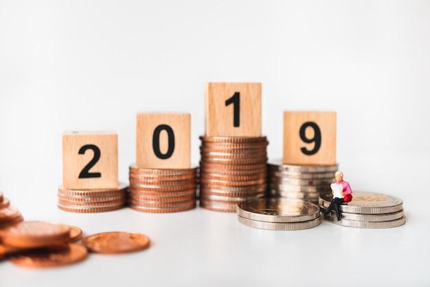 Pessoas em miniatura, mulher lendo na pilha de moedas com o ano de 2019 Foto Premium