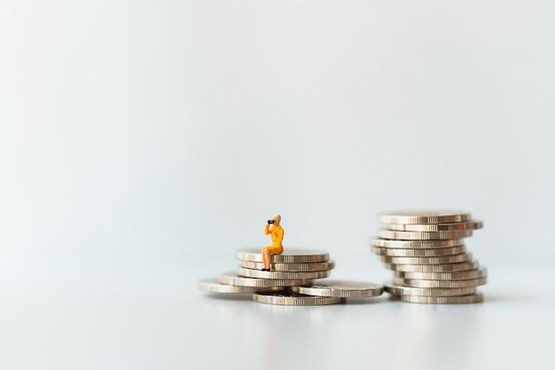 Pessoas em miniatura, mulher sentada na pilha de moedas usando como negócio e conceito financeiro Foto Premium