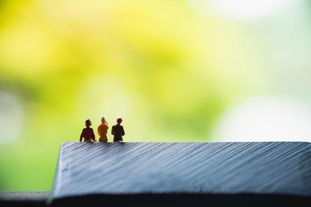 Pessoas em miniatura, mulher sentada no banco na natureza verde fundo usando para recursos humanos de negócios Foto Premium