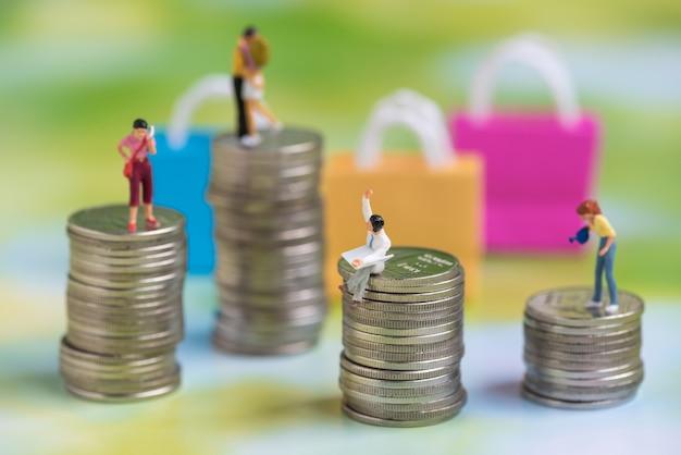 Pessoas em miniatura na pilha de moedas Foto Premium