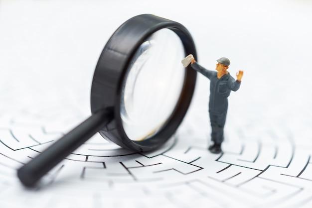 Pessoas em miniatura: o empresário usa lupa para encontrar a rota no labirinto. Foto Premium