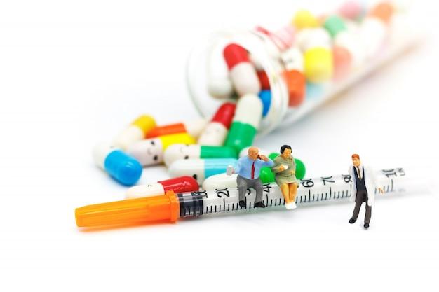 Pessoas em miniatura: pacientes gordos sentado na seringa com drogas. conceito de cuidados de saúde. Foto Premium