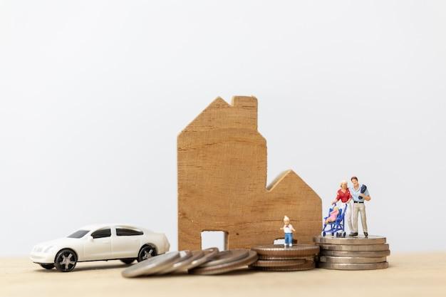 Pessoas em miniatura: pais com filhos com casa e empilhamento de moedas Foto Premium