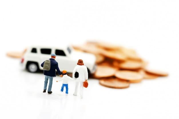 Pessoas em miniatura: pais e filhos caminhando para o modelo de carro com moedas. conceito de dinheiro, finanças e empréstimo de carro. Foto Premium
