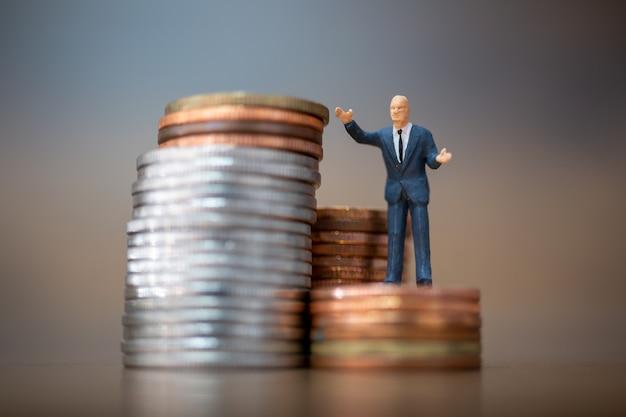 Pessoas em miniatura: pequenos empresários em pé com uma pilha de moedas, conceito de crescimento do negócio. Foto Premium