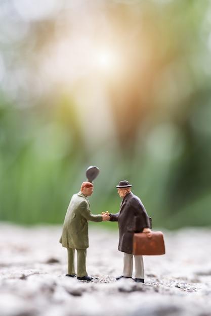 Pessoas em miniatura: pessoas de negócios, reunião de saudação, apertando as mãos cena ao ar livre Foto Premium