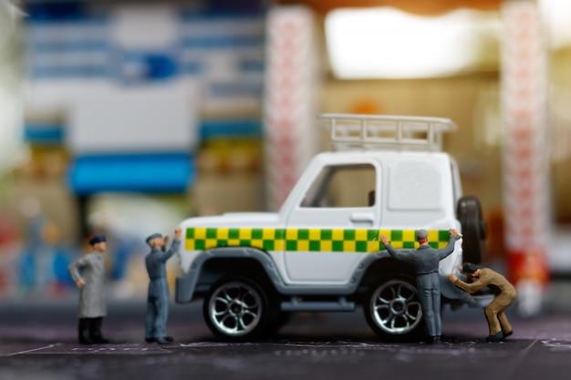 Pessoas em miniatura, reparando o carro Foto Premium