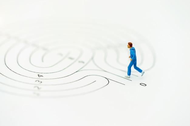 Pessoas em miniatura rodando no ponto de partida do labirinto e pensando em como resolver esse problema. Foto Premium