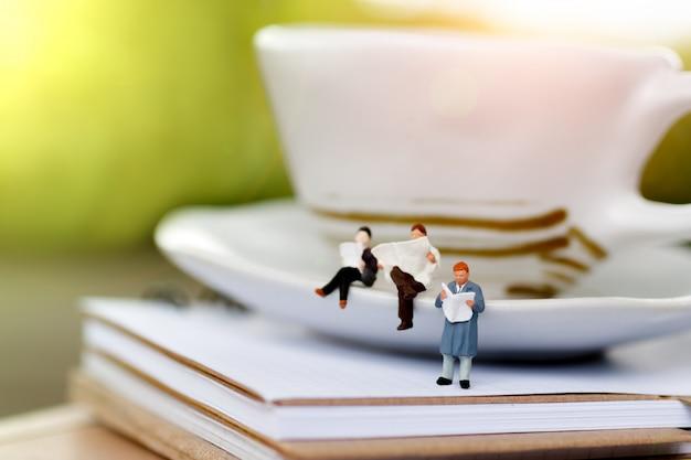 Pessoas em miniatura, sentado em uma xícara de café Foto Premium