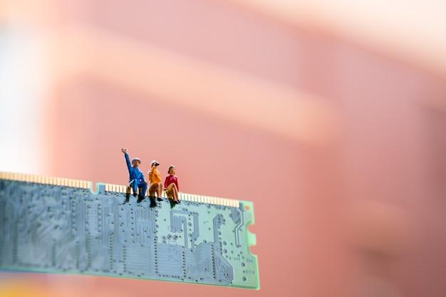 Pessoas em miniatura, sentado na placa de circuito Foto Premium