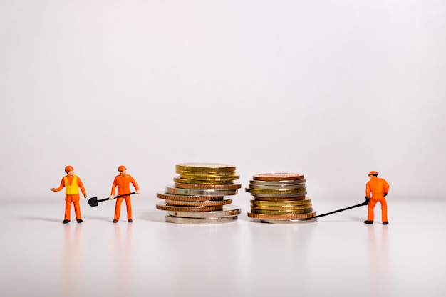 Pessoas em miniatura, técnico trabalhando em moedas de pilha Foto Premium