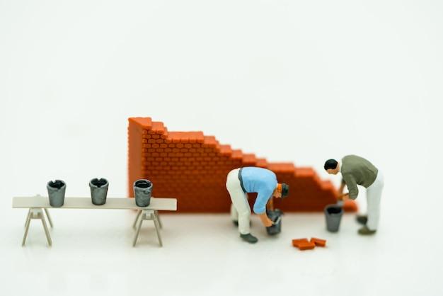 Pessoas em miniatura, trabalhando em uma parede Foto Premium