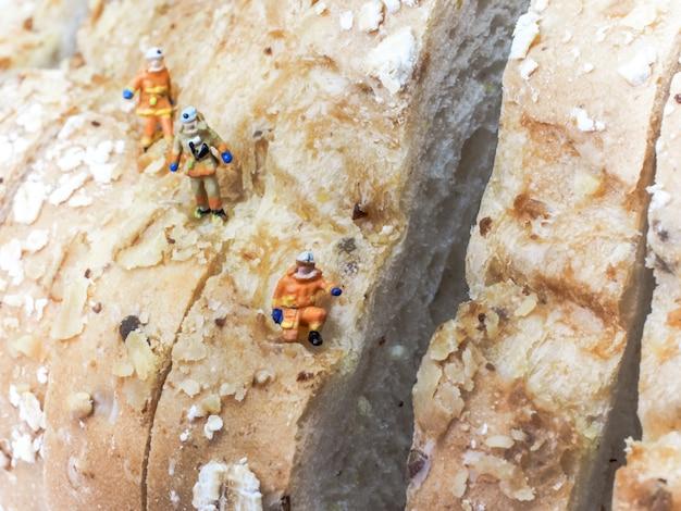 Pessoas em miniatura: três exploradores estão subindo uma montanha de quilos de pão. Foto Premium