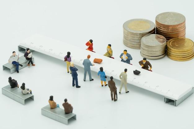 Pessoas em miniatura usam depósito em dinheiro. no balcão do banco ou instituição financeira. Foto Premium